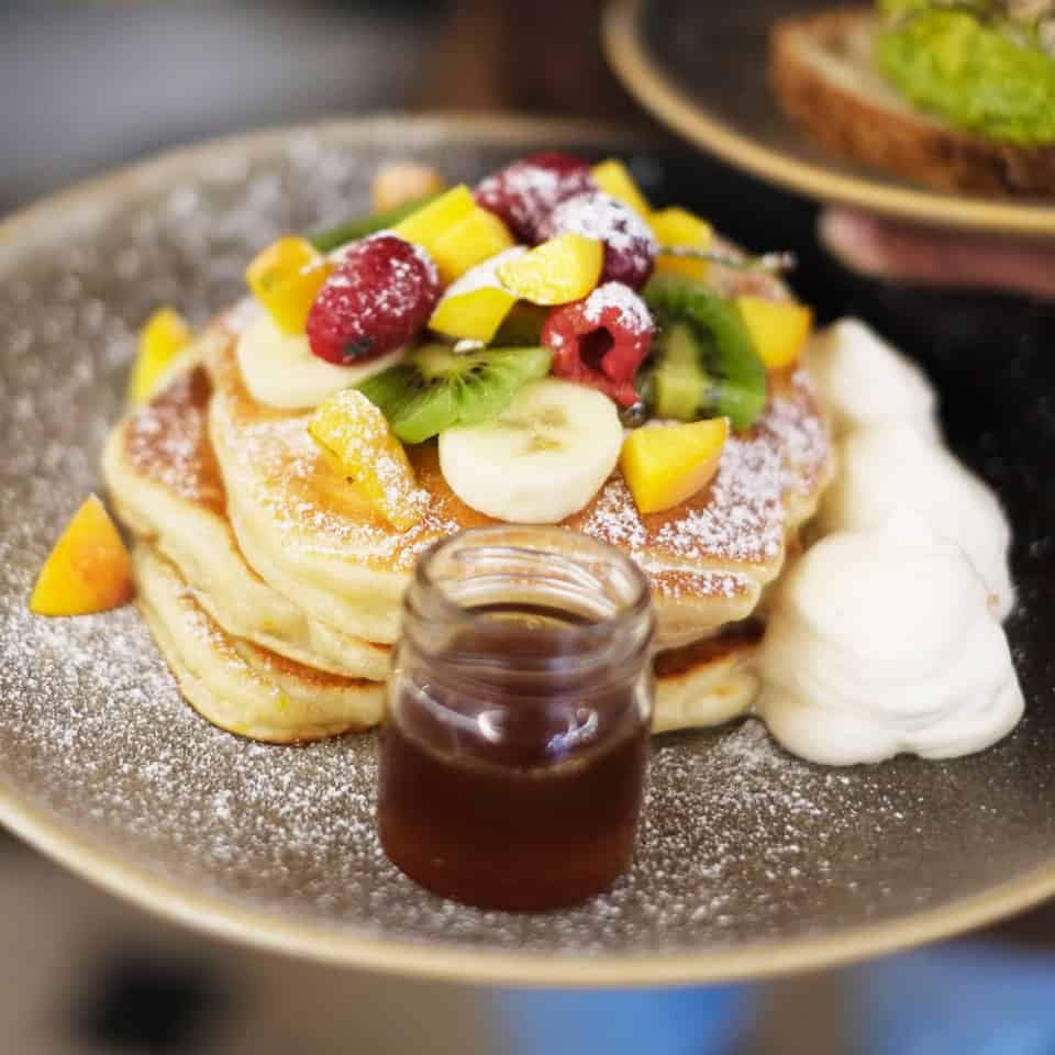 Pancakes with fresh fruit, maple syrup and whipped cream