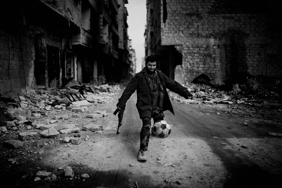 Andoni Lubaki: An Islamist fighter playing among the ruins. Aleppo, Syria 2013.