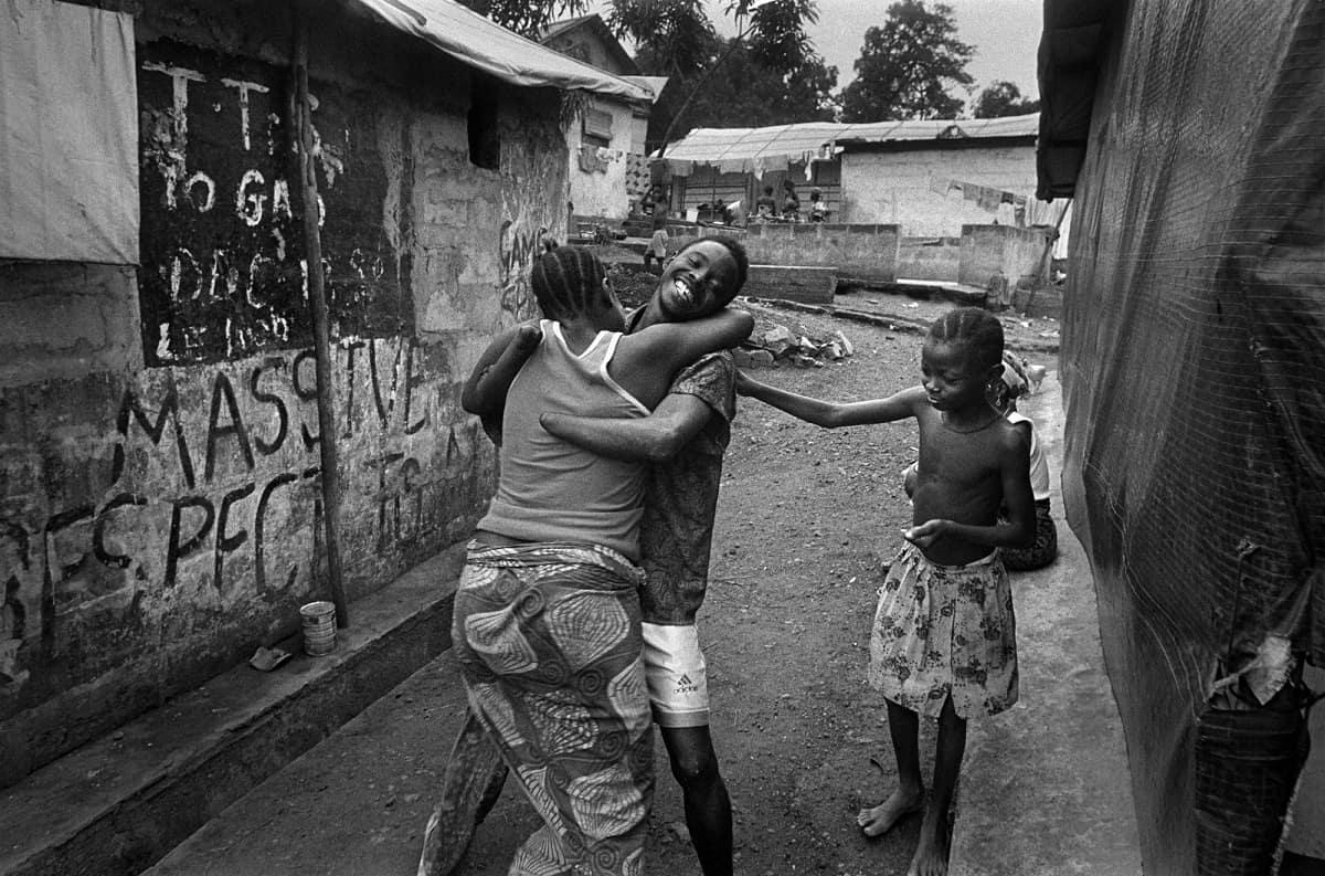 Gervasio Sánchez: A victim of amputation embraces family. Freetown, Sierra-Leone 2000.