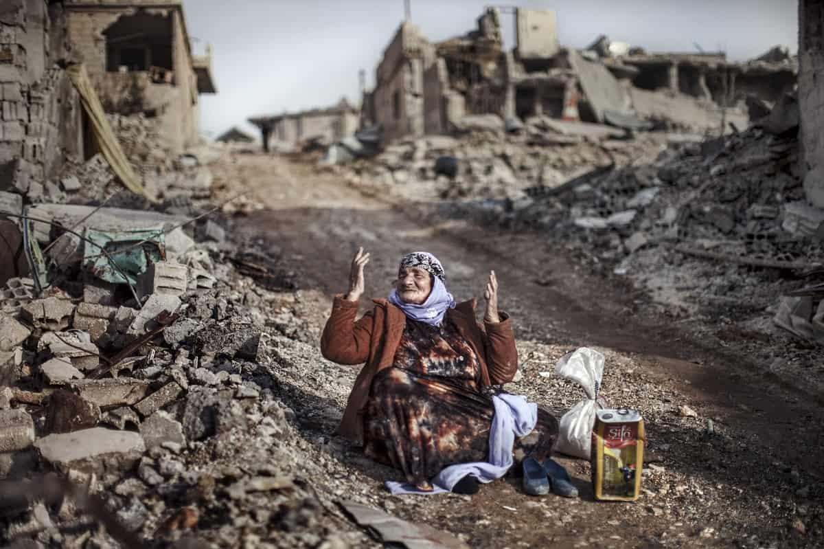 JM Lopez: Kurdish woman in front of her destroyed house. Kobanî, Syria 2015.
