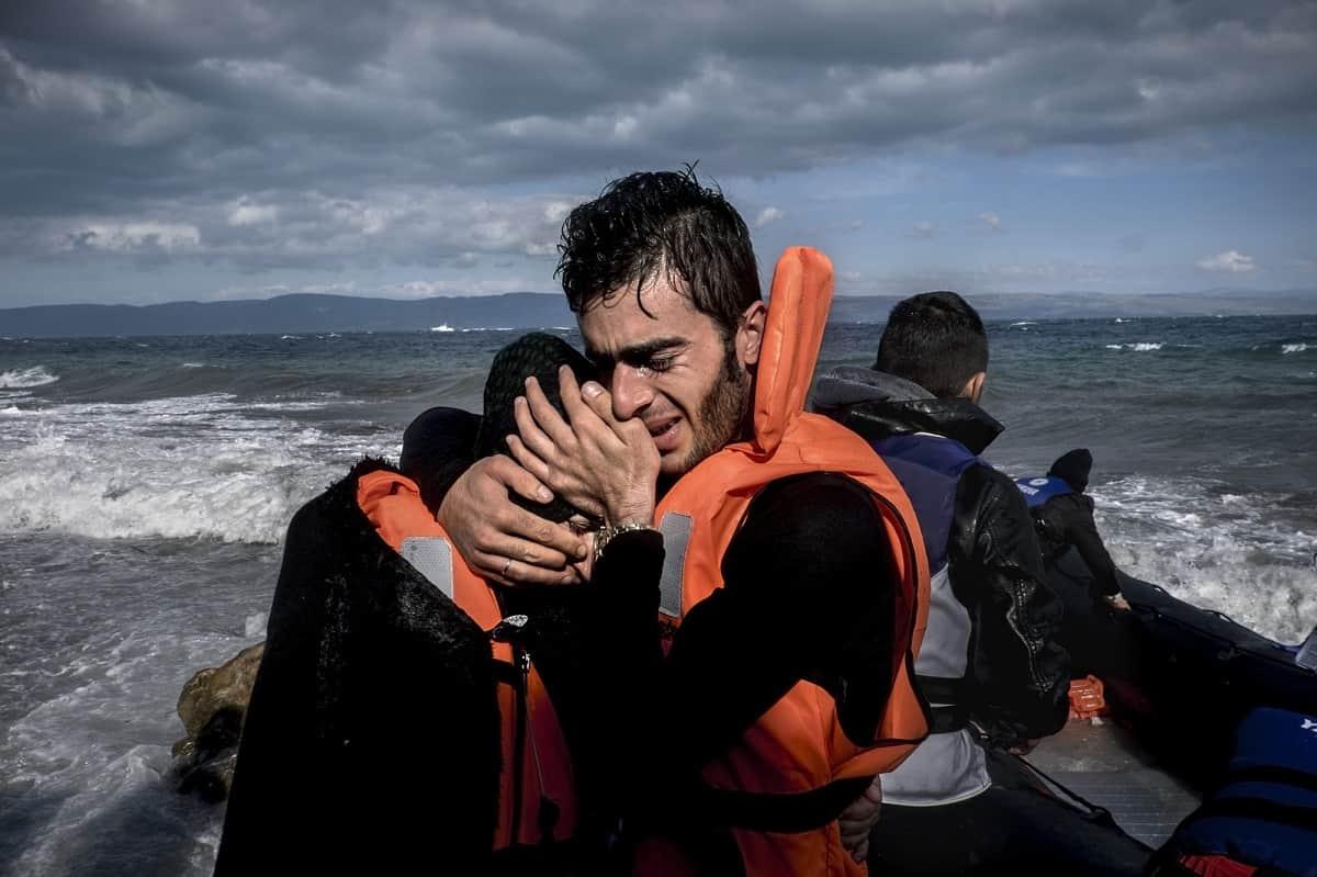 Javier Bauluz: Refugees celebrate their survival on arriving in Lesbos, Greece (2015).